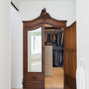Design ideas for a modern gender neutral walk-in wardrobe in Austin with travertine flooring.