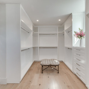 Exempel på ett stort modernt walk-in-closet för könsneutrala, med öppna hyllor, vita skåp, ljust trägolv och brunt golv