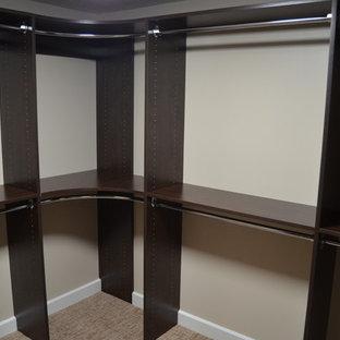 Ispirazione per una cabina armadio unisex classica di medie dimensioni con ante marroni, moquette e nessun'anta