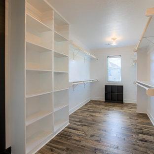 Imagen de armario vestidor unisex, campestre, grande, con armarios estilo shaker, puertas de armario blancas, suelo de madera pintada y suelo marrón