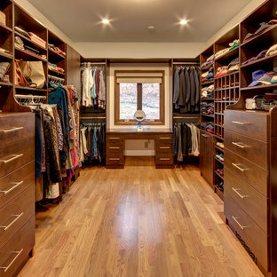 Large elegant gender-neutral medium tone wood floor and beige floor walk-in closet photo in Other with flat-panel cabinets and dark wood cabinets