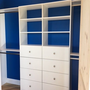 Reach-in closet - large traditional gender-neutral medium tone wood floor and brown floor reach-in closet idea in Other with flat-panel cabinets and white cabinets