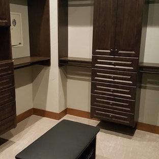 Cette photo montre un très grand dressing chic neutre avec un placard avec porte à panneau surélevé, des portes de placard en bois sombre, moquette et un sol beige.