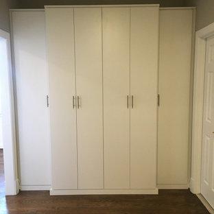 Diseño de armario y vestidor minimalista, grande, con puertas de armario blancas y suelo de madera oscura
