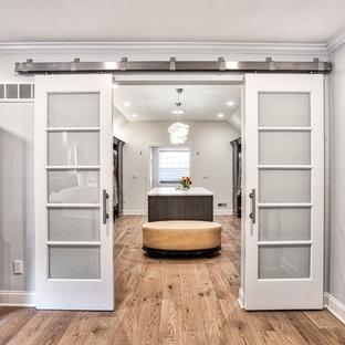 ニューヨークの巨大な男女兼用トランジショナルスタイルのおしゃれなウォークインクローゼット (濃色木目調キャビネット、淡色無垢フローリング、フラットパネル扉のキャビネット) の写真