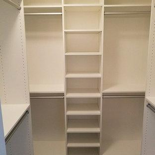 Idée de décoration pour un petit dressing craftsman avec un placard à porte plane, des portes de placard blanches, moquette et un sol marron.