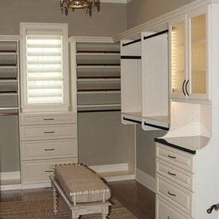 Ispirazione per una grande cabina armadio per donna minimal con ante di vetro, ante bianche, parquet scuro e pavimento beige
