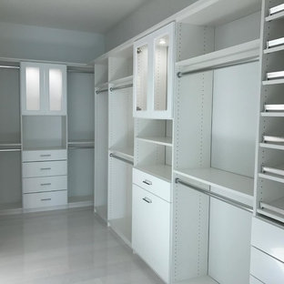 This is an example of a large romantic gender neutral walk-in wardrobe in Other with glass-front cabinets, white cabinets, travertine flooring and beige floors.