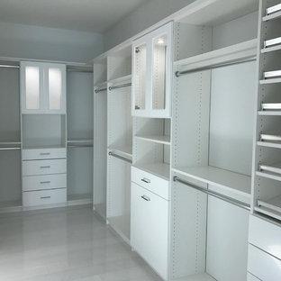 Foto di una grande cabina armadio unisex shabby-chic style con ante di vetro, ante bianche, pavimento in travertino e pavimento beige