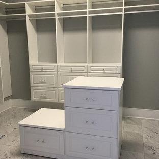 Diseño de armario vestidor unisex, tradicional, extra grande, con armarios con paneles con relieve, puertas de armario blancas y suelo de mármol