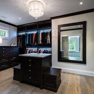 Esempio di un grande spazio per vestirsi unisex chic con ante con riquadro incassato, ante in legno bruno, pavimento in legno massello medio e pavimento marrone