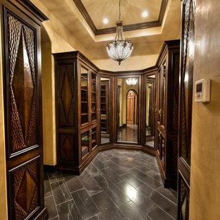 Diseño de armario vestidor de hombre, tradicional, de tamaño medio, con armarios con paneles con relieve, puertas de armario de madera oscura y suelo de pizarra