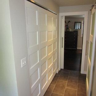 Imagen de armario unisex, moderno, pequeño, con puertas de armario blancas y suelo de baldosas de porcelana
