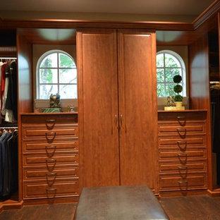 Ejemplo de armario vestidor de hombre, clásico, de tamaño medio, con armarios con paneles con relieve, puertas de armario de madera oscura y suelo de madera oscura