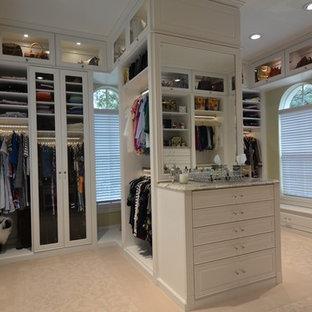 Esempio di una grande cabina armadio per donna chic con ante di vetro, ante bianche e moquette