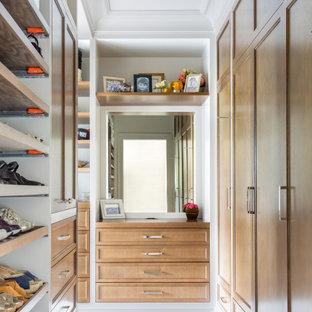 Ejemplo de armario vestidor de mujer, clásico renovado, con armarios con paneles empotrados, puertas de armario de madera oscura y suelo gris