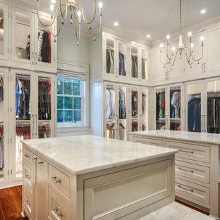 Geräumiger, Neutraler Klassischer Begehbarer Kleiderschrank mit Glasfronten, weißen Schränken, braunem Holzboden, braunem Boden und gewölbter Decke in New Orleans