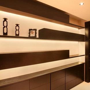 Ispirazione per una cabina armadio moderna di medie dimensioni con ante lisce e ante in legno bruno