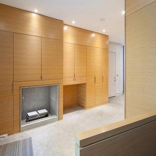 Ispirazione per una grande cabina armadio unisex moderna con ante lisce, ante in legno chiaro e pavimento in pietra calcarea