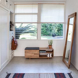 Ejemplo de vestidor unisex, contemporáneo, pequeño, con armarios con paneles lisos, puertas de armario blancas y suelo de cemento