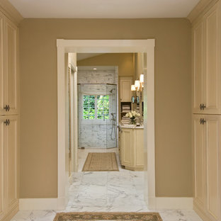 Example of an island style walk-in closet design in New York with beige cabinets