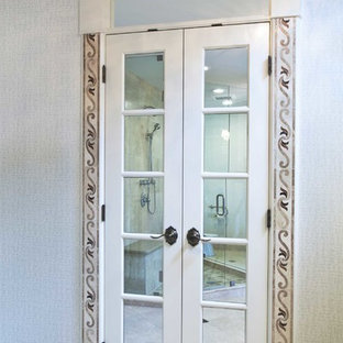 Design ideas for a medium sized traditional gender neutral walk-in wardrobe in Kansas City with recessed-panel cabinets, white cabinets and travertine flooring.