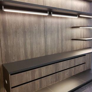 Ispirazione per una grande cabina armadio unisex design con ante lisce, ante in legno scuro, pavimento in cemento e pavimento nero