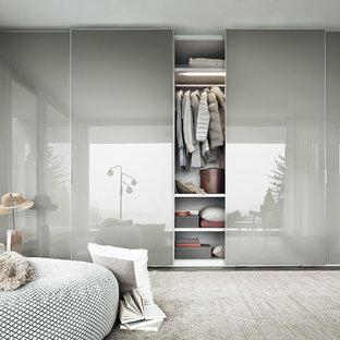 Ispirazione per un armadio o armadio a muro unisex minimalista di medie dimensioni con ante di vetro, ante bianche, parquet scuro e pavimento marrone