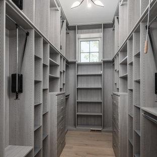 Inredning av ett modernt stort walk-in-closet för kvinnor, med släta luckor, grå skåp, ljust trägolv och beiget golv