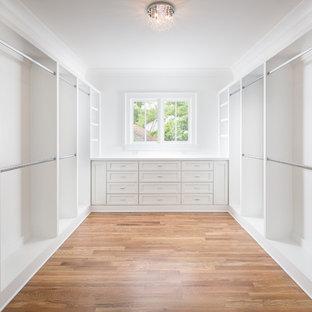 Diseño de armario vestidor clásico, extra grande, con armarios con paneles empotrados, puertas de armario blancas y suelo de madera en tonos medios
