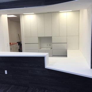 Foto de armario y vestidor minimalista con armarios con paneles lisos, puertas de armario blancas, suelo de madera oscura y suelo multicolor