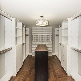 Bild på ett stort funkis walk-in-closet för könsneutrala, med vita skåp, mörkt trägolv och brunt golv