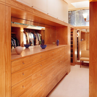 This is an example of a mid-sized modern gender-neutral walk-in wardrobe in Boston with flat-panel cabinets, medium wood cabinets and carpet.