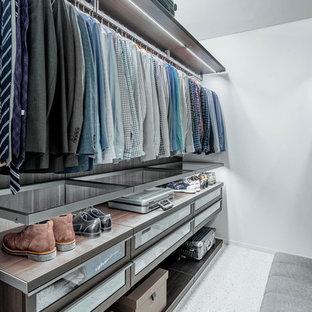 Esempio di una grande cabina armadio per uomo moderna con ante di vetro, ante in legno bruno, pavimento in laminato e pavimento bianco
