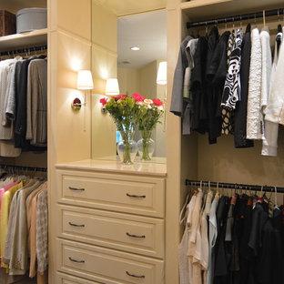 Exemple d'un grand dressing chic pour une femme avec un placard avec porte à panneau surélevé, des portes de placard blanches et un sol en bois foncé.
