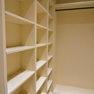 Example of a large classic women's dark wood floor walk-in closet design in DC Metro with raised-panel cabinets and white cabinets