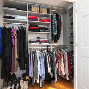 Imagen de armario unisex, contemporáneo, de tamaño medio, con armarios abiertos, puertas de armario grises, suelo de madera en tonos medios y suelo naranja
