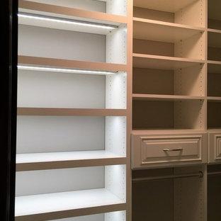 Exempel på ett mellanstort klassiskt walk-in-closet, med luckor med upphöjd panel, vita skåp och heltäckningsmatta