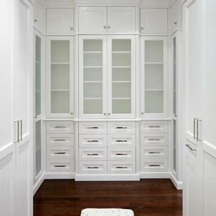Immagine di un'ampia cabina armadio per donna chic con ante con riquadro incassato, ante bianche e parquet scuro