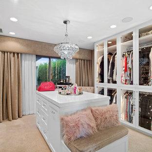 オレンジカウンティの女性用トロピカルスタイルのおしゃれなフィッティングルーム (ガラス扉のキャビネット、白いキャビネット、カーペット敷き、ベージュの床) の写真