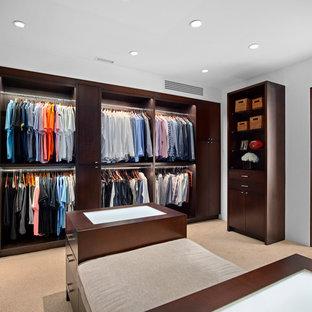 Modelo de vestidor de hombre, exótico, con armarios abiertos, puertas de armario de madera en tonos medios, moqueta y suelo beige