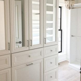 Ejemplo de vestidor de mujer, romántico, pequeño, con armarios con paneles empotrados, puertas de armario blancas, suelo de madera clara y suelo beige