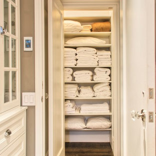 Example of a small classic gender-neutral medium tone wood floor reach-in closet design in Orange County with open cabinets and white cabinets