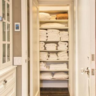 Diseño de armario unisex, tradicional, pequeño, con armarios abiertos, puertas de armario blancas y suelo de madera en tonos medios