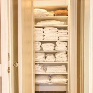 Modelo de armario unisex, clásico, pequeño, con armarios abiertos, puertas de armario blancas y suelo de madera en tonos medios