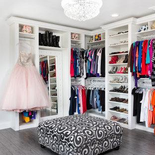 Imagen de vestidor de mujer, actual, extra grande, con armarios con paneles con relieve, puertas de armario blancas y suelo de madera oscura