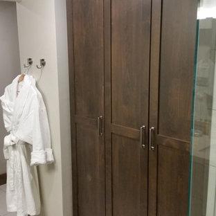 ソルトレイクシティの中くらいの男女兼用トラディショナルスタイルのおしゃれなフィッティングルーム (シェーカースタイル扉のキャビネット、茶色いキャビネット、テラコッタタイルの床、白い床) の写真