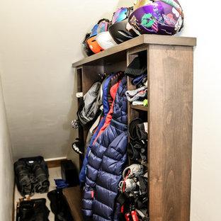 Ejemplo de armario vestidor unisex, minimalista, de tamaño medio, con armarios estilo shaker, puertas de armario de madera oscura, suelo de travertino y suelo blanco