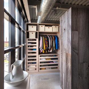Ejemplo de armario vestidor unisex, industrial, de tamaño medio, con armarios abiertos y puertas de armario de madera clara
