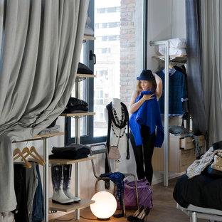Modelo de vestidor de mujer, urbano, grande, con armarios abiertos y suelo de madera en tonos medios